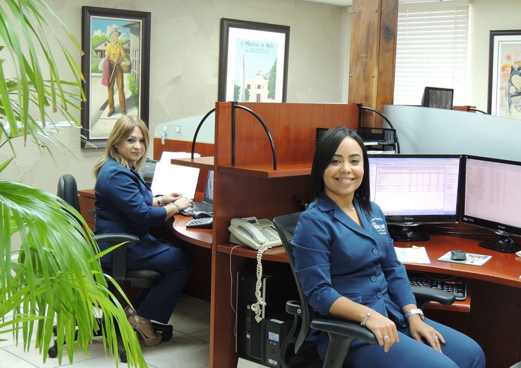 Two women smiling from their office desks