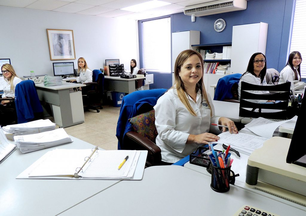 A group of working women smiling from their office desks